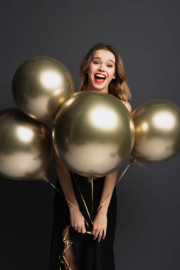 Happy young woman in black slip dress holding golden balloons on grey stock vector