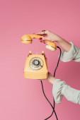 Ausgeschnittene Ansicht einer Frau mit Vintage-Telefon und Hörer isoliert auf rosa