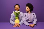 mladý africký americký pár sedí v blízkosti vázy s tulipány izolované na fialové
