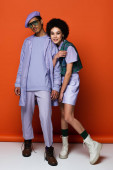 full length of trendy african american couple smiling on orange