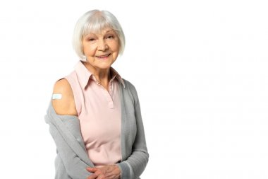 Positive elderly woman with adhesive plaster on arm looking at camera isolated on white stock vector