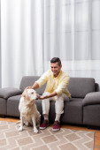 labrador dog sticking out tongue near cheerful man sitting on couch at home