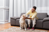 cheerful man sitting on couch and cuddling labrador dog