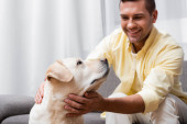 vidám férfi simogatás labrador kutya otthon, homályos háttér