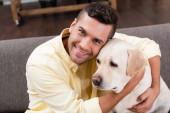 fiatal férfi átöleli labrador kutya, miközben mosolyog a kamera