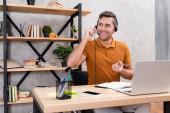 radostný muž ve sluchátkách pracuje doma čistý notebook a smartphone s prázdnou obrazovkou