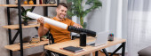 smiling architect putting paper into poster tube while sitting near laptop, banner