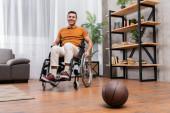 radostný muž se usmívá na kameru, zatímco sedí na vozíku poblíž basketbalu na podlaze