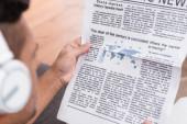 levágott kilátás férfi fülhallgató olvasás újság elmosódott előtérben