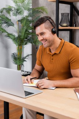 Disabled man looking at laptop while working in headset in home office stock vector