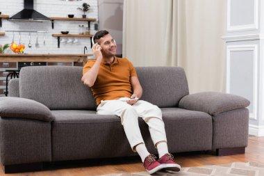 Joyful man holding smartphone while listening music in headphones on sofa stock vector