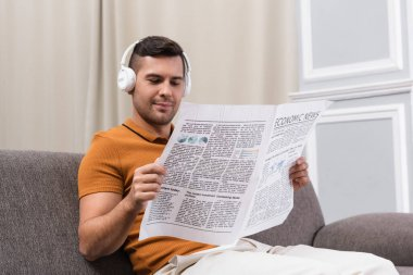 Positive man in wireless headphones reading newspaper on sofa at home stock vector