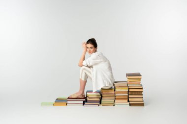 Full length of smiling young woman in sandals sitting on pile of books on white stock vector