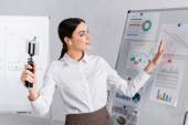 Lächelnde Geschäftsfrau mit Kopfhörer zeigt bei Video-Chat auf Handy im Büro auf Flipchart