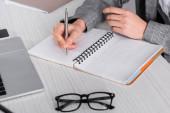 Vágott kilátás üzletasszony írás notebook közelében szemüveg és laptop