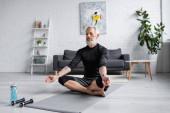 muž s šedivými vlasy meditující na podložce jógy v blízkosti činek v obývacím pokoji, prapor