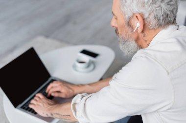 bearded man in wireless earphones using laptop with blank screen
