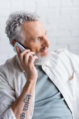 Tattooed and bearded man with grey hair talking on cellphone stock vector