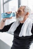 bearded man with grey hair drinking water from sports bottle