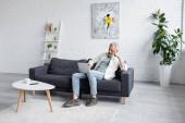 Mann mit grauen Haaren benutzt Laptop, während er auf Couch neben Tasse Kaffee und Smartphone mit leerem Bildschirm auf Couchtisch sitzt