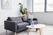 šťastný vousatý muž s šedými vlasy sedí na gauči a pomocí notebooku v obývacím pokoji