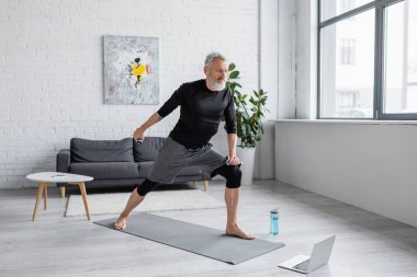 barefoot man with grey hair exercising with dumbbells near laptop in living room