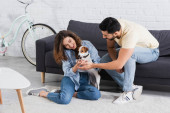 smiling woman cuddling jack russell terrier near muslim boyfriend