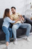 usmívající se interracial pár mazlení jack Russell teriér v obývacím pokoji