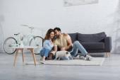 veselý mezirasový pár objímání v blízkosti jack Russell teriér v moderním obývacím pokoji
