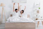 bdělý mezirasový pár dívá na sebe při protahování v posteli