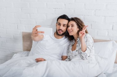 Bearded muslim man taking selfie while happy woman showing peace sign in bedroom stock vector