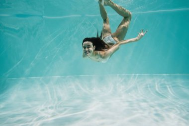 Happy young woman in white swimsuit diving in pool stock vector