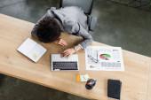 Felső nézet afro-amerikai üzletasszony feküdt közelében laptop, dokumentum és notebook az asztalon