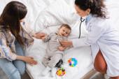 Blick von oben auf einen afrikanisch-amerikanischen Kinderarzt im weißen Kittel, der einen kleinen Jungen mit Stethoskop untersucht