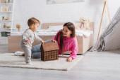šťastná matka při pohledu na dům model v blízkosti kojence syna na koberci