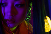neon lighting on face of young blurred asian woman with dragon earring