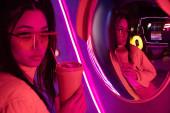 stylische junge asiatische Frau mit Sonnenbrille posiert mit Pappbecher in der Nähe von Spiegel und Neonbeleuchtung