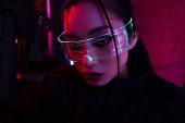 brünette asiatische Frau mit künstlicher Narbe mit Pistole und Blick auf die Kamera