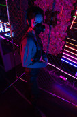high angle view of young asian woman in gas mask and headphones standing near neon lighting