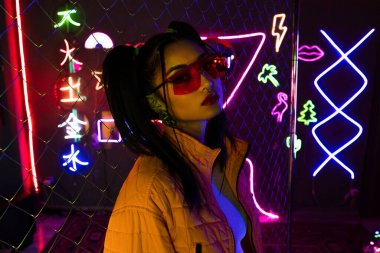 Young asian woman in sunglasses looking at camera near neon sign stock vector