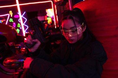 Armed asian woman in sunglasses holding gun stock vector