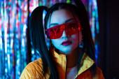 brünette junge asiatische Frau mit Sonnenbrille schaut auf Kamera draußen