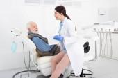 Lächelnder Zahnarzt zeigt älteren Patienten in Zahnklinik Tablette