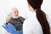Seniorin im Zahnarztstuhl lässt sich vom Arzt in der Klinik beraten