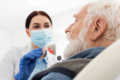 dentist in medical mask examining teeth of senior man with probe and mirror in dental chair