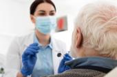 zubař v lékařské masce vyšetření zubů seniora se sondou a zrcadlem v zubním křesle