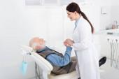 Lächelnder Zahnarzt hält Hände eines älteren Patienten, der im Zahnarztstuhl liegt