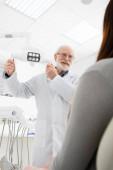 fröhliche Seniorin berührt medizinische Lampe vor Frau im Zahnarztstuhl