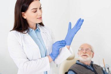 Dentist in white coat adjusting latex gloves near elderly patient sitting in dental chair stock vector