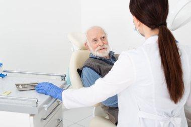 Smiling senior man getting consultation from dentist in latex gloves in dental clinic stock vector